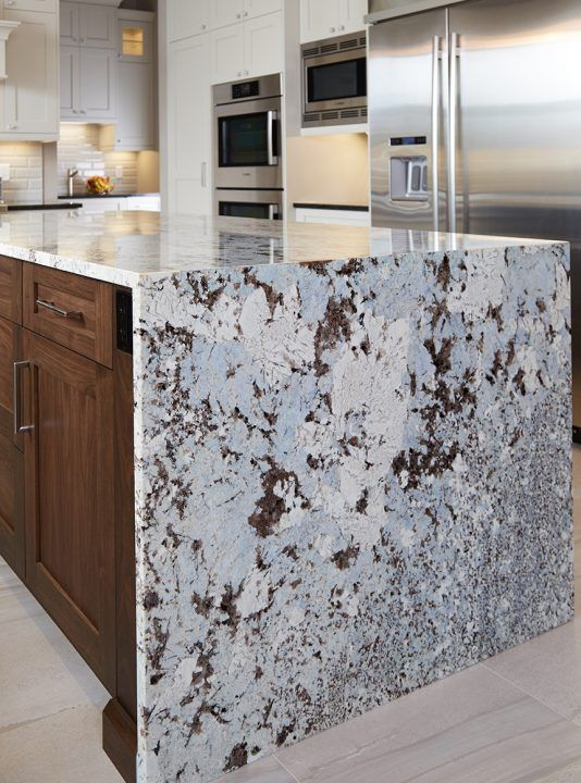 We love this show stopping island! Love the various patterns the granite counertop gives with the waterfall edge. The contrast of the warm white cabinets and brown island cabinets make this kitchen feel traditional and inviting.