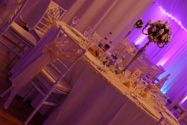 Sfeșnice cu flori ca aranjament central al meselor de invitați.