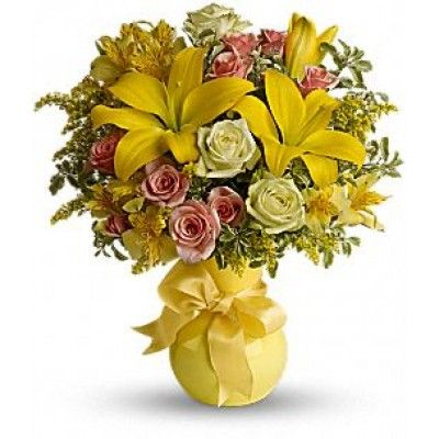 A joyous celebration of friendship, or a fun one to send just because. This warm yellow assortment of lilies, roses, alstroemeria and assorted greens are presented in a lovely yellow vase that's tied with a yellow bow.