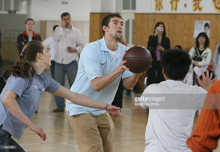 Olympic and World Swimming champions Katie Hoff (L) and Michael Phelps (C), play basketball against disabled students from the Pudong Special Needs School, in Shanghai, 13 April 2007. Phelps and Hoff are in Shanghai on a goodwill tour to promote the 2007 Special Olympics to be held in October. AFP PHOTO/Mark RALSTON