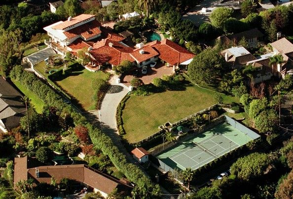 John Travolta clearly enjoys a large front lawn (and tennis court, and pool).