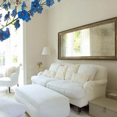 A long mirror turned sideways can pull double-duty as a piece of art when positioned above a couch that is equally as long.