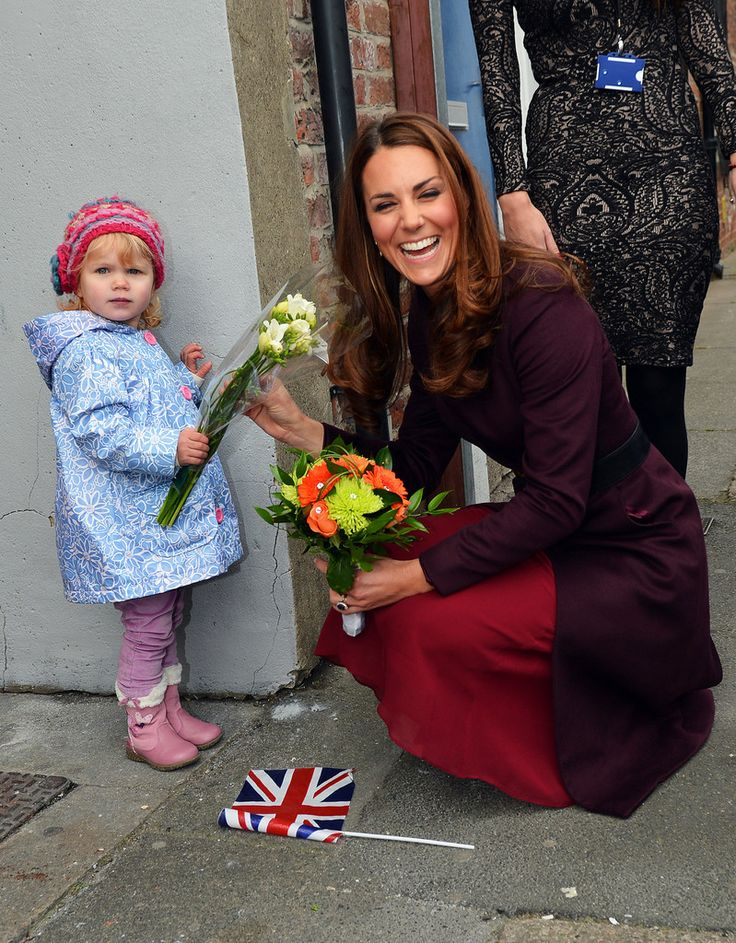 Kate Middleton Photos - Catherine, Duchess of Cambridge laughs as she receives flowers from two-year-old Lola Mackay - who refused to let go of them - during a visit to the CRI Stockton Recovery Service on October 10, 2012 in Stockton-On-Tees, England. - The Duchess Of Cambridge Visits The North East