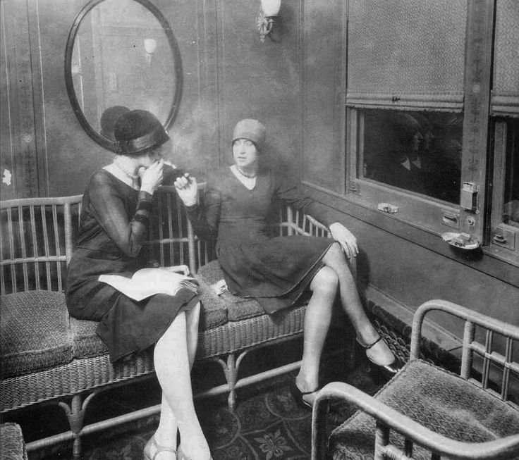 Flappers smoking cigarettes in a train car (1920s)