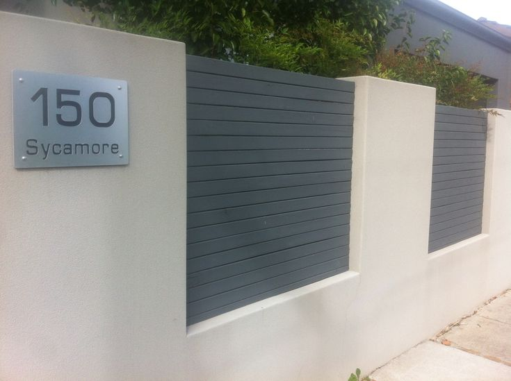 Rendered fence, large house no. Aluminium slats to soften fence look. Needs hedge above and colour change of wall to suit house colour.