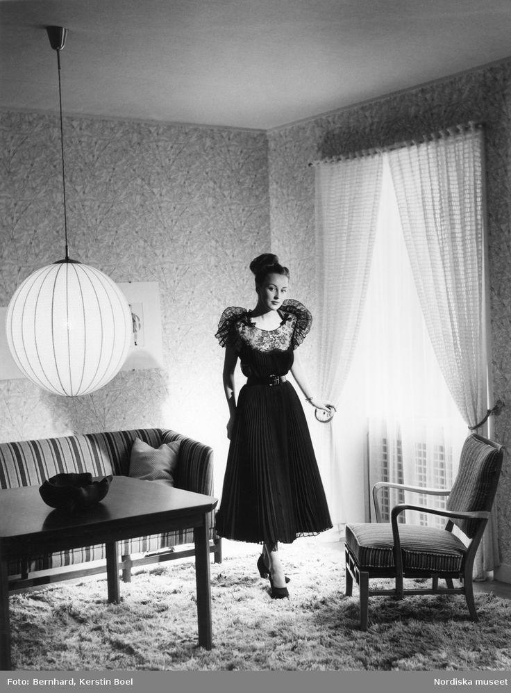 Modell i svart plisserad klänning med puffärmar i spets, ballerinaknut och mörka pumps, i ett vardagsrum med Ryamatta på golvet. Fotograf: Kerstin Bernhard, ca 1955-1960