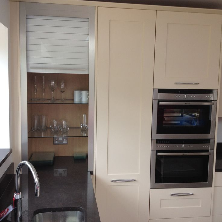 Contemporary kitchen with embedded breakfast bar and beige cabinets. L-Shaped layout. Hidden storage for glassware.