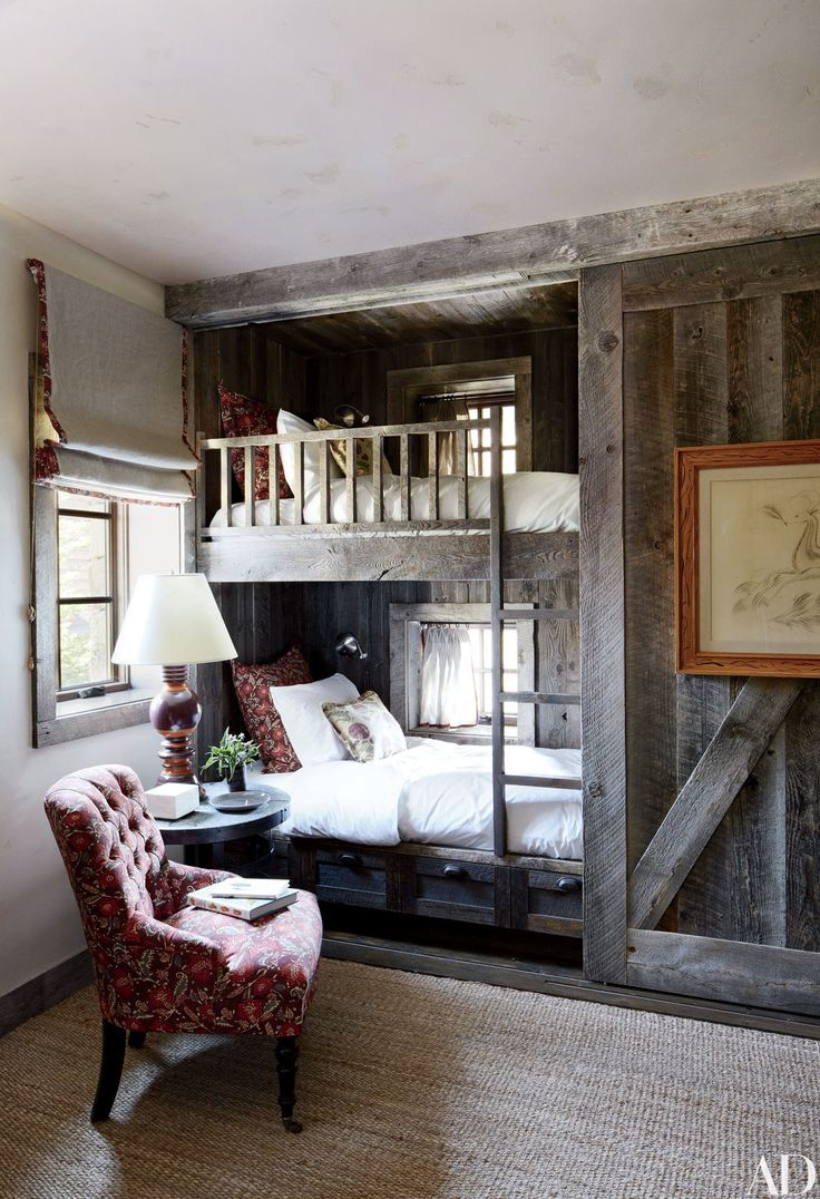 The bunk room in a Montana home decorated by Markham Roberts is partially sheathed in reclaimed corral boards.