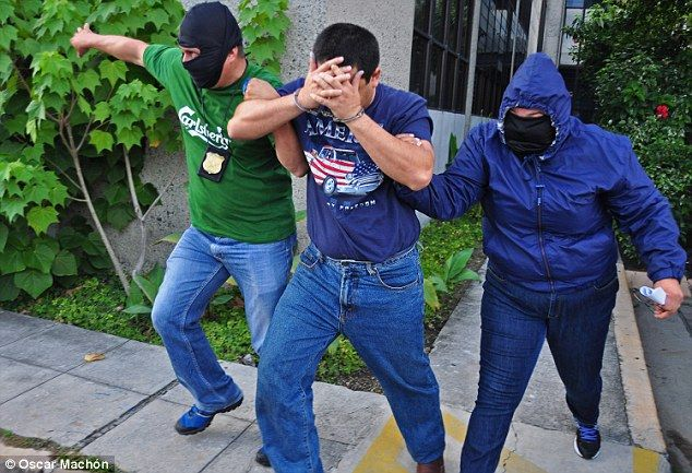 Seized: Dr Alejandro Guido is taken away in handcuffs by police in San Salvador. They acte...