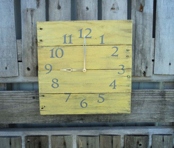 This clock is made from reclaimed pallet wood. Painted yellow, with grey numbers, and features silver colored metal clock hands. Runs on a quartz