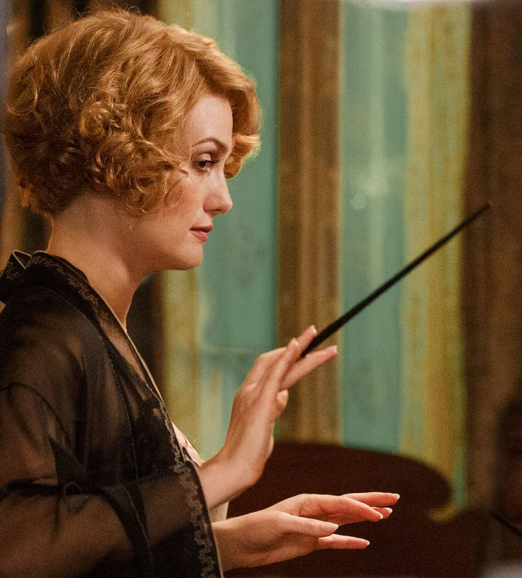 """This wand belonged to Queenie Goldstein. Its wood and core materials are unknown. Behind the scenes This wand will appear in the film adaptations of Fantastic Beasts and Where to Find Them. The wand design was influenced by actress Alison Sudol and was meant to reflect Queenie's personality — reports describe it as """"sexy"""" and with an Art Deco-inspired design."""