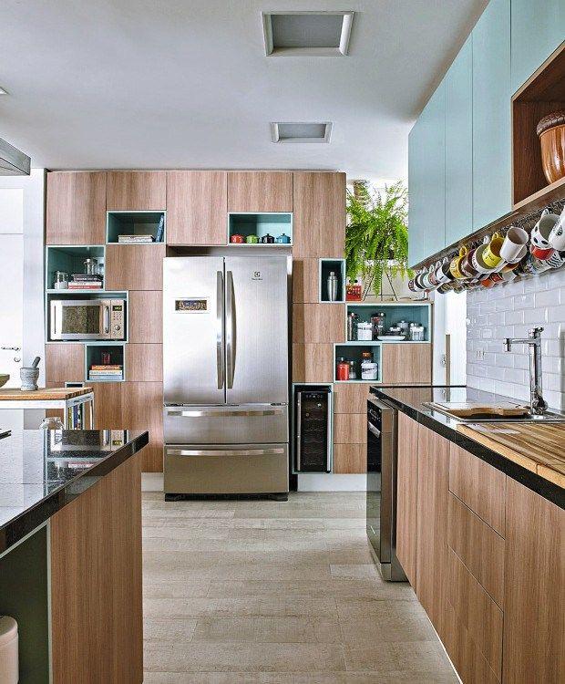 Cozinha com marcenaria marrom e nichos azul claro, bancadas de granito preto, fogão cooktop na bancada em ilha, piso cerâmico cinza. Em uma das paredes azulejos brancos subway. Decoração de Apartamento em Higienópolis, São Paulo