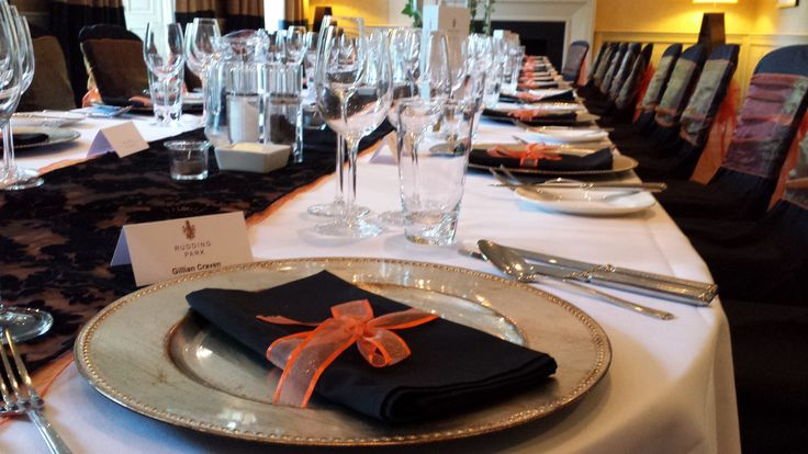 Black napkin with orange ribbon on gold charger plate at Rudding Park