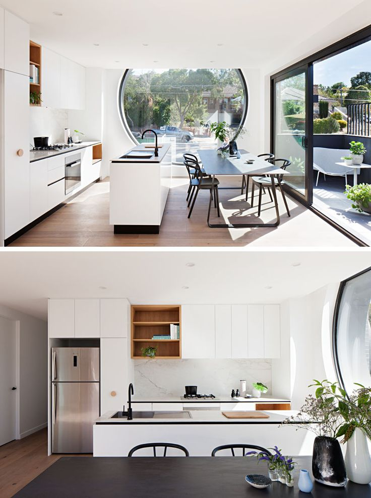 This kitchen is minimal in design, with a long island separating the dining room and a wall of kitchen cabinets. Open wood shelving breaks up the all white cabinets, and a large porthole window floods the room with natural light. #Kitchen #ModernKitchen #WhiteCabinets #DiningRoom #InteriorDesign