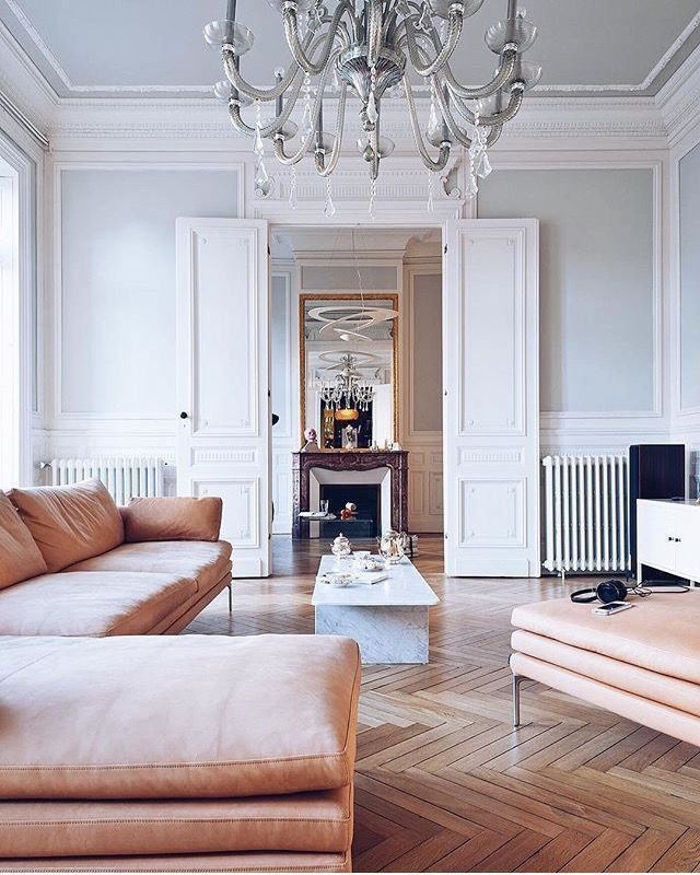 Parquet wooden flooring in a grand Parisian style apartment. Double doors leading to another reception room, old school style radiators, dusky pink sofa