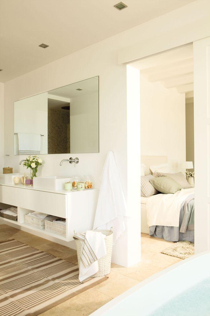 Un baño abierto al dormitorio con un lavamanos doble y un mueble volado en blanco