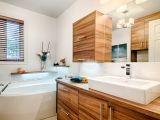 Le bois aux teintes variées des armoires donnent un look exotique à cette salle de bain moderne.