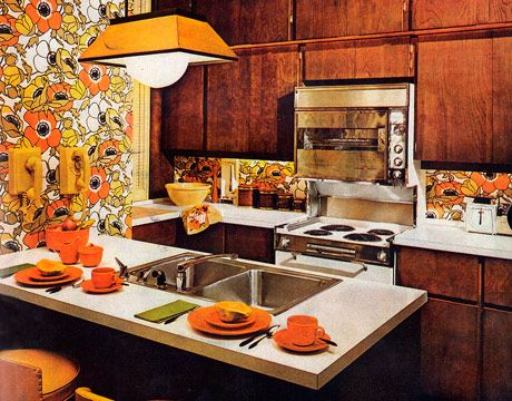 "This Manhattan apartment kitchen, designed by Robert Caigan Associates, was the epitome of sophisticated living in 1968. ""The strong solids of white, walnut, sun yellows are given buoyancy and a delicate linkage by the wallpaper, its flowers colored to order,"" according to the pages of House Beautiful. ""A room in praise of the fact that city dwellers need not sacrifice space and sunniness"