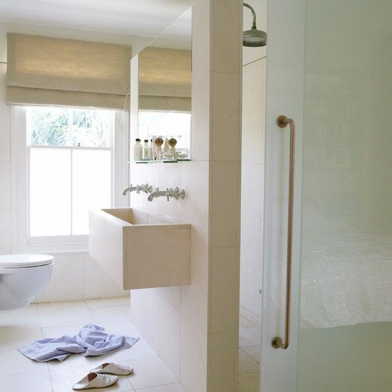 Open-plan wet room with shower behind sink