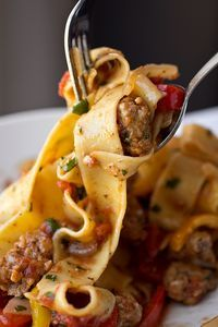 "Italian Drunken Noodles - Saucy, Italian ""Drunken"" Noodles with Spicy Italian Sausage, Tomatoes and Caramelized Onions and Red and Yellow Bell Peppers, with Fresh Basil."