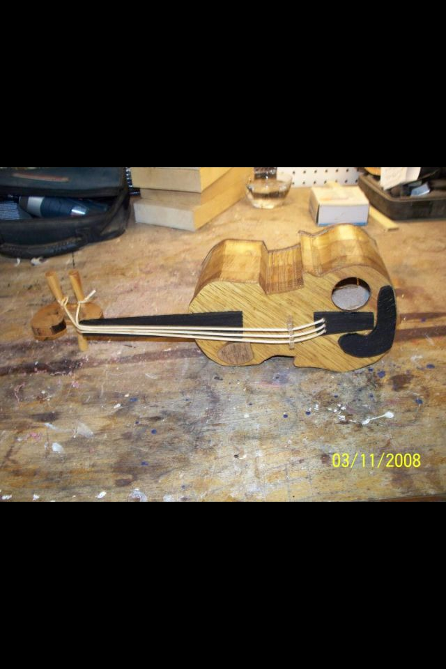 The Fiddlers Inn, made from all oak and walnut. Strings are even wood.  One exception, the hinge for the clean out is brass.  As you can see by the date on the pic, I began making these some time ago.