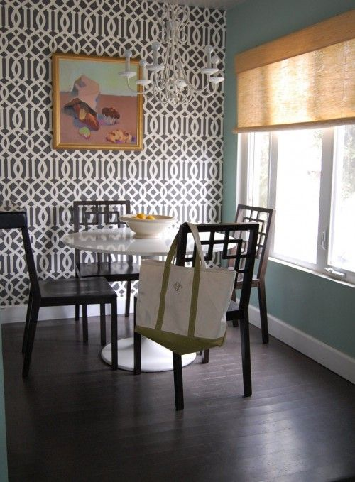Chic dining room design with turquoise walls paint color, bamboo roller shade, Ikea Docksta dining table, West Elm overlapping squares dining chairs and Kelly Wearstler Imperial Trellis wallpaper.