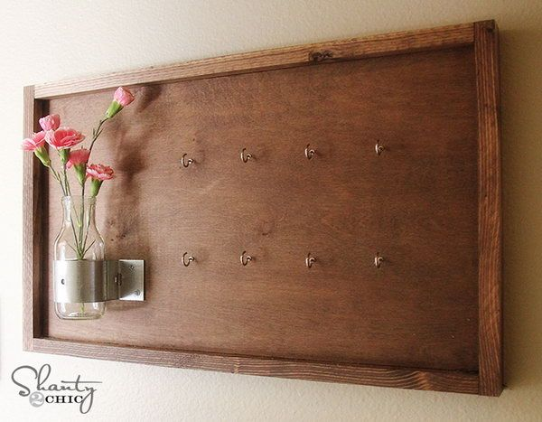 DIY Key Holder Decorated with Vase and Flowers.  This version of a key holder features an old board but decorated with vases and flowers. It looks good on the wall, replacing beautifully any painting or artwork, but holding your keys as well. See more