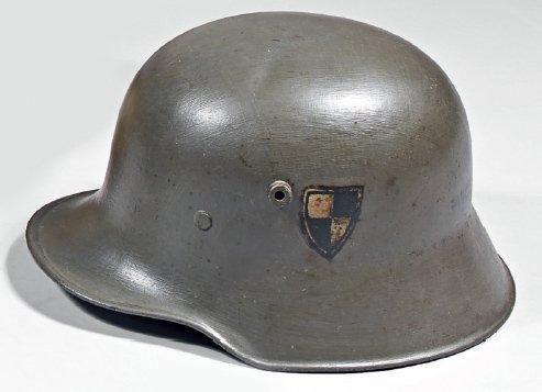 Un casque allemand en tôle d'acier couleur kaki, cocarde en forme d'écu à quatre quartiers peints en noir et blanc (peinture kaki reprise); époque 1914/1918