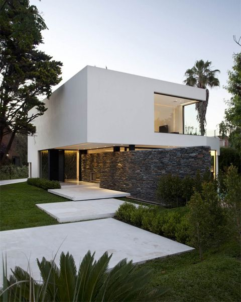 Andres Remy Arquitectos designed this house on an irregular lot with rustic and crafted stone that defines and separates the entry zones from the living spaces.