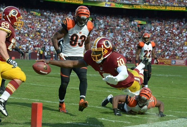 Redskins quarterback Robert Griffin III dives for the goal line in the third quarter against Cincinnati. Griffin came up short but set up a touchdown pass to Santana Moss to tie the score.  Jonathan Newton / The Washington Post