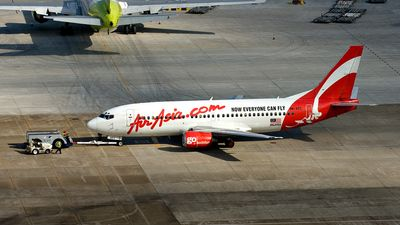 AirAsia (MY) Boeing 737-3Y0 9M-AEC aircraft, with the sticker ''Air Asia Com.'' in red letters, ''Now Everyone Can Fly''in black letters on white airframe & go holiday'' in white letters at airplane engine, pussed off for departure at China Macau International Airport. 08/07/2007.