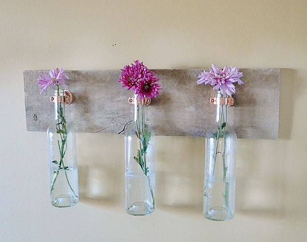 Bring your garden inside by placing flowers into a hanging wine bottle display.