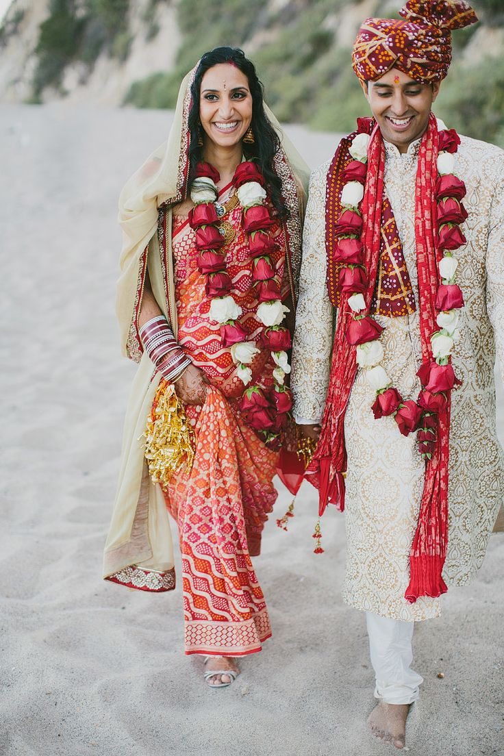 Hindu wedding ceremony with traditional gold, red and orange palette. Beautiful red and white rose garland