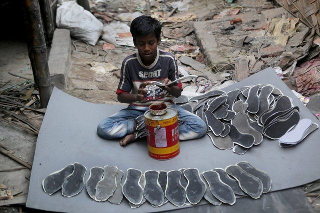 Indian boy Hassan Malik works in a leather shoe factory at Topsia in Calcutta, eastern India, 19 November 2013. (Photo by Piyal Adhikary/EPA...