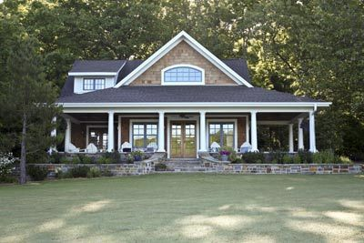 Front elevation of the lake cottage with its wide wrap porch. Located in Bella Vista, Arkansas on Lake Windsor by architect Chip Chambers. 2of2