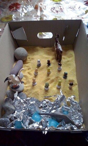 Sensory box con farina gialla, sassi, alluminio e ghiacciolini.