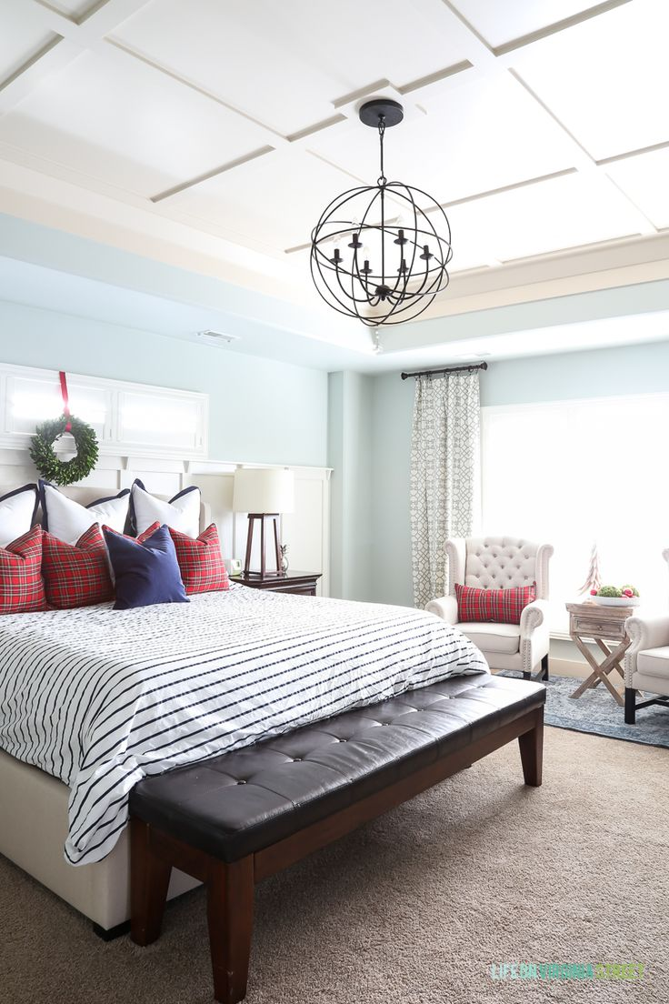 A traditional Christmas master bedroom, decorated with red, navy blue, white and plaid and boxwood wreaths. Such a pretty space!