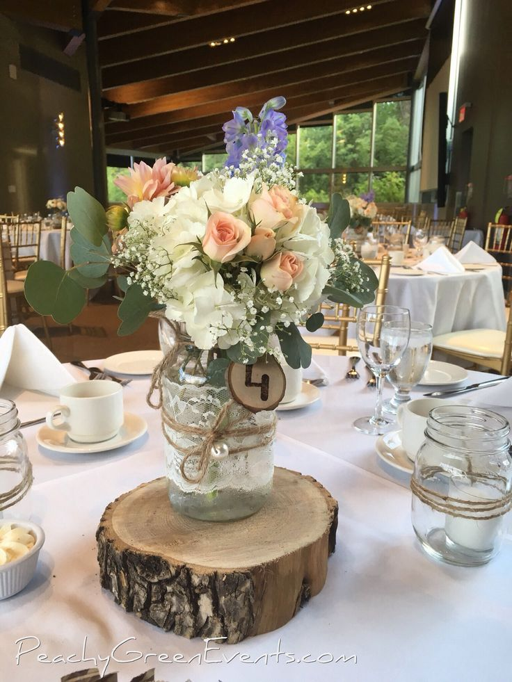 Table 4, wooden disk with lace wrapped mason jar, rustic burnt wood table number and white, peach and purple flowers for a wedding Qualico Family Centre in Winnipeg