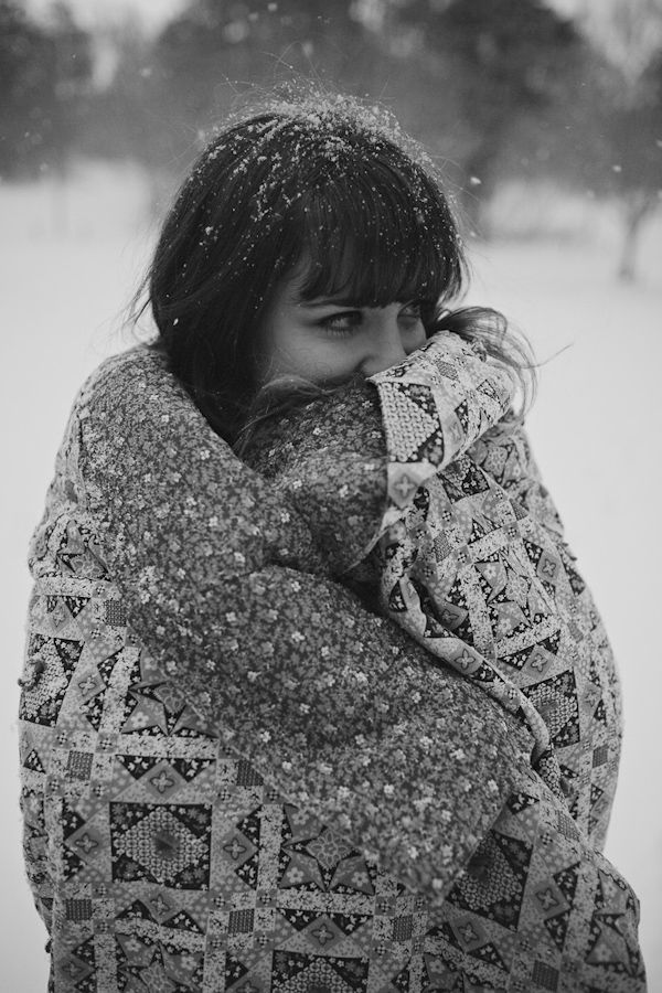 snowy, winter engagement shoot - adorable black and white photo of bride-to-be wrapped in blanket in the snow - photo by Michigan based wedding photographers Bryan and Mae