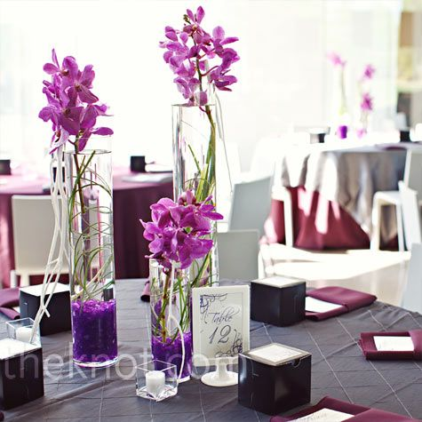 The recipe for these striking centerpieces: glass cylinders filled with bear grass and fuchsia orchids.