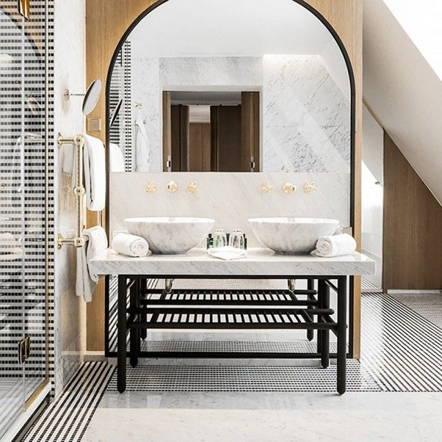 French hotel bathroom with carrara marble tiles, and a marble sink