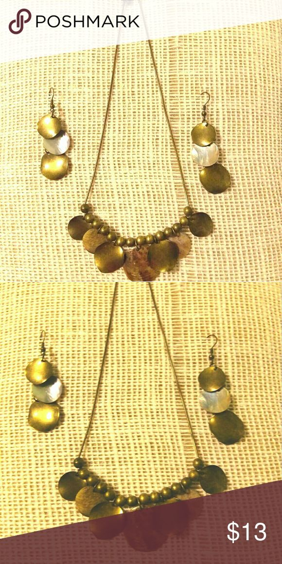 Necklace and earring set. Necklace and earrings set. The color is a bronze metal with she'll round pieces.  The necklace has a thin chain.  There are bronze beads and wavy round metal bronze and shell pieces.   The earrings are for pierced ears?.  It has two metal pieces and a shell piece that dangle down.   Pet free and smoke free home. Jewelry