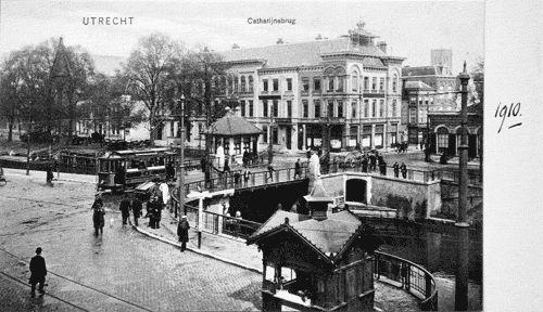 De Catharijne-barrière in 1910, gezien vanaf de Leidseweg (nu: Smakkelaarsveld). Rechts op de brug het brugwachtershuisje, op de voorgrond een kiosk. Het gebouw rechts was een politiebureau, dat gebouwd was na afbraak van de Catharijnepoort. Tot 1865 deed het ook dienst als commiezenhuis, waar belasting werd geïnd. Dit gebied werd rond 1910 nog steeds 'Catharijne-barrière' genoemd, ook al was de poort verdwenen. Zo is  benaming 'Tolsteeg-barrière' nu nog steeds in gebruik.