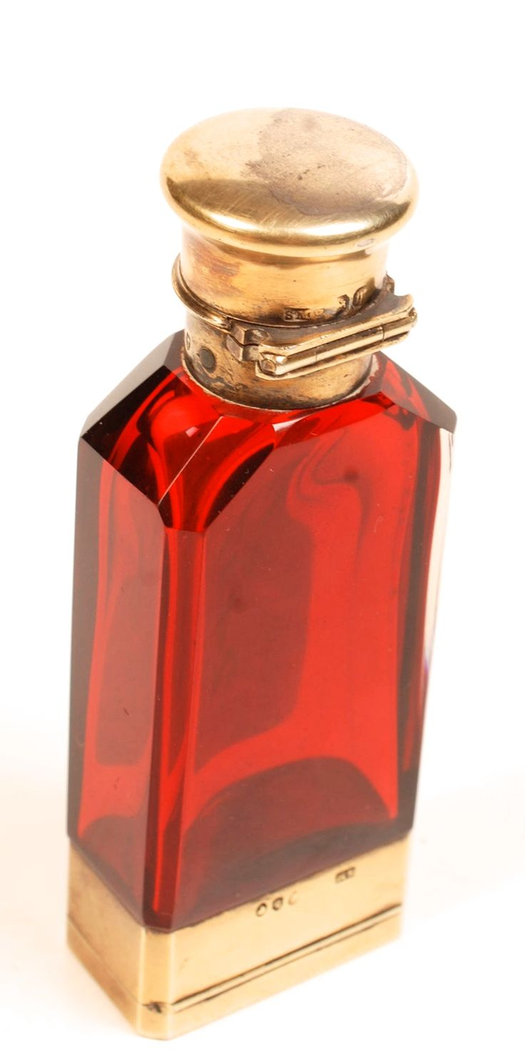 Perfume Bottle: A Mappin & Webb perfume bottle in red glass with silver gilt mounts.  The base opens up to reveal a vesta case.