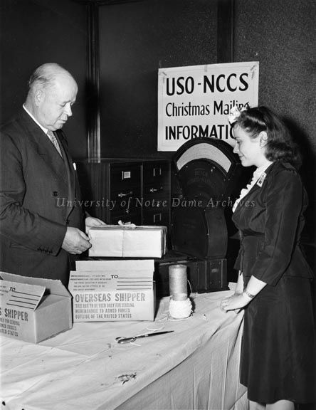 Post Master General Frank C. Walker, Notre Dame Law School Class of 1909, and Miss Helen Richards of Hazelton, Pennsylvania (PA) work the USO-NCCS overseas Christmas Mailing Booth, National Catholic Community Service, Washington, D.C., ca.1943 | University of Notre Dame Archives