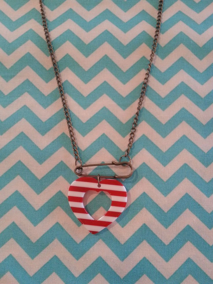 Safety pin and heart necklace.