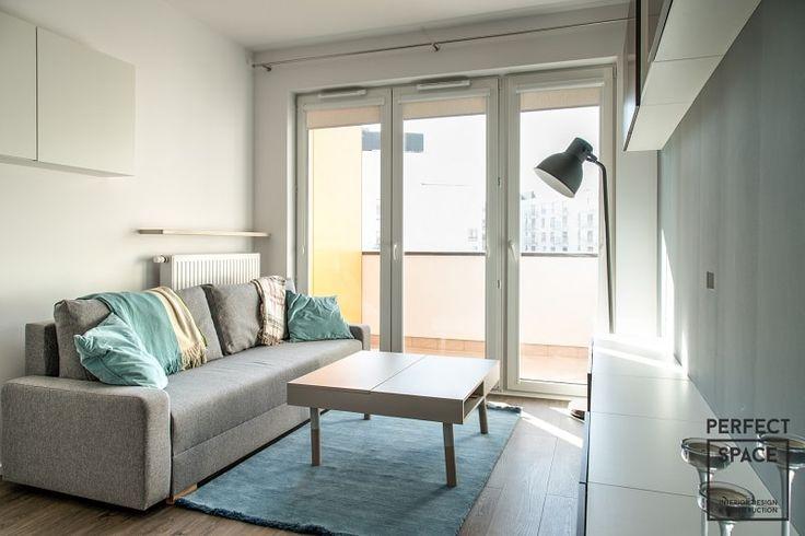 Wnętrze salonu - jasne i przestronne z wyjściem na balkon. Salon z białymi meblami i szarą sofą.