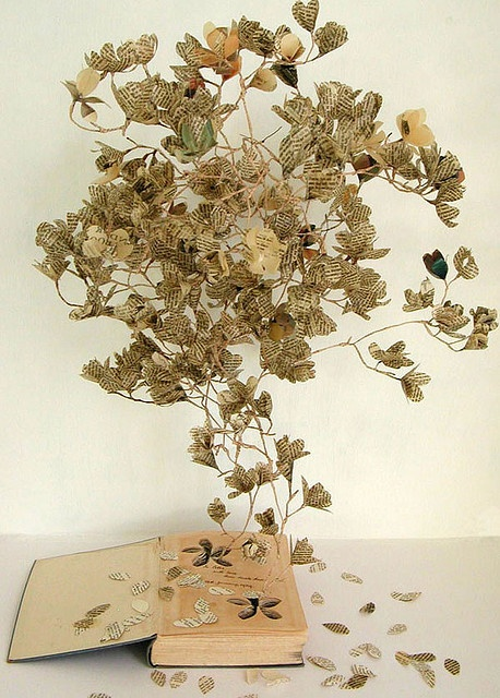Cut down tree, make paper, make book, mold pages, make tree. It's almost like a twisted loop. The leaves and the flowers help make this tree more. I also like tha I can't really tell if the tree is emerging from the book or beside it or from thin air.   book art #book #art