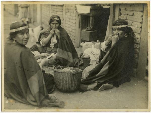 [Tres mujeres mapuches, con su vestimenta y joyas típicas, se encuentran descalzas y están sentadas en el suelo] | Reproducción del original, fotografía digital. Ca. 1925