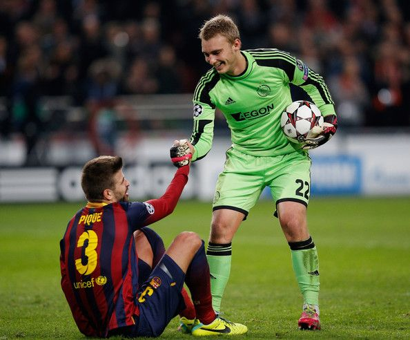 Jasper Cillessen of Ajax helps Gerard Pique of Barcelona up during the UEFA Champions League Group H match between Ajax Amsterdam and FC Barcelona at Amsterdam Arena on November 26, 2013 in Amsterdam, Netherlands.
